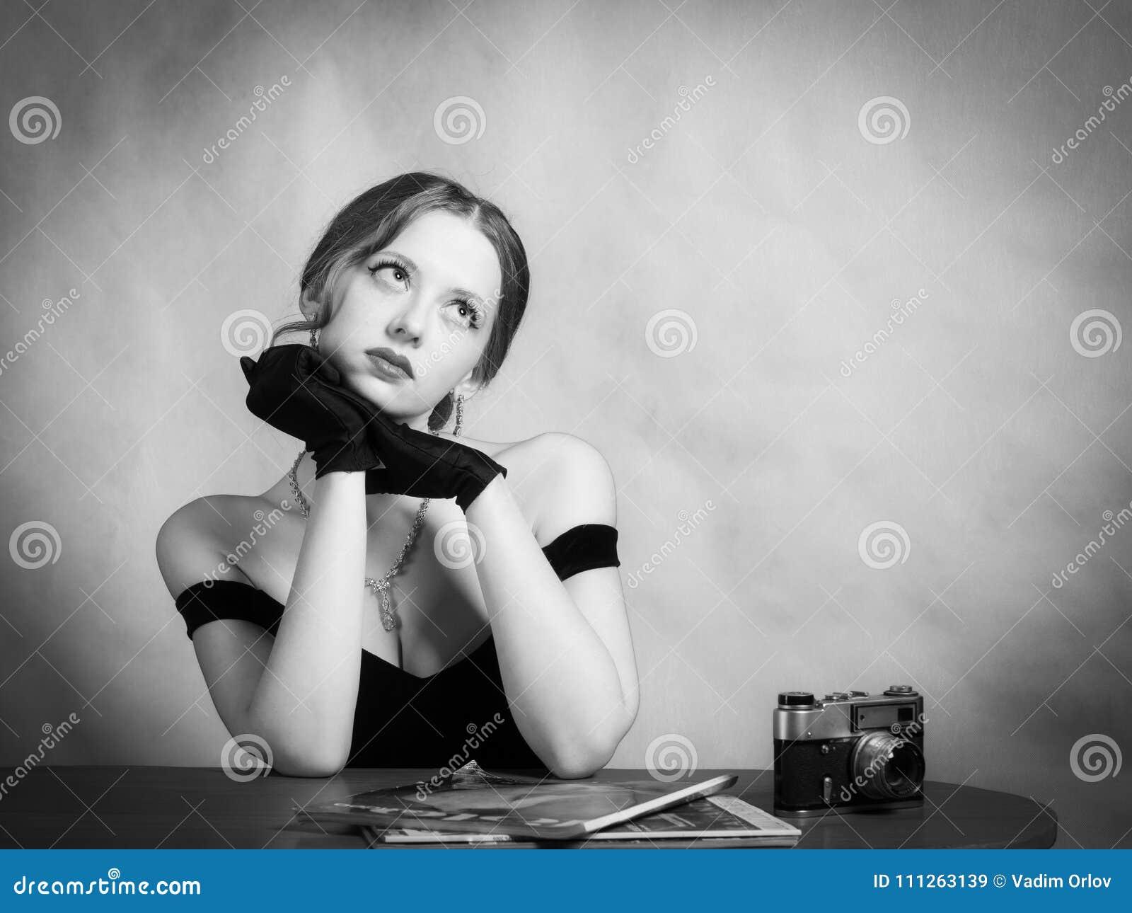 Nachdenkliches Mädchen im Abendkleid, das bei Tisch mit Zeitschriften sitzt