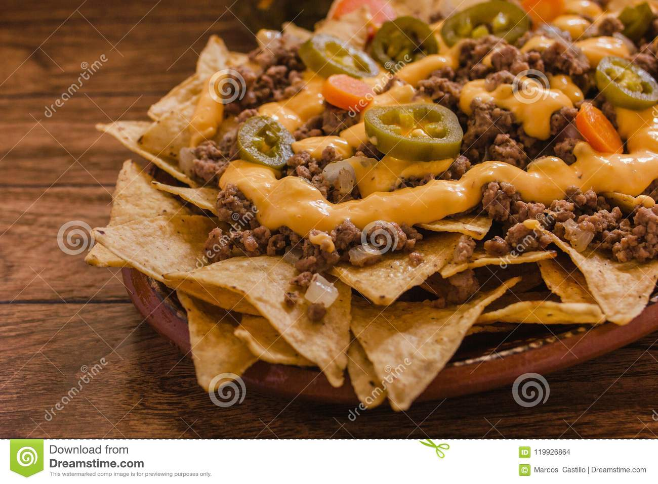 Nacho chips corn garnished with ground beef, melted cheese, jalapeño peppers, mexican spicy food in mexico