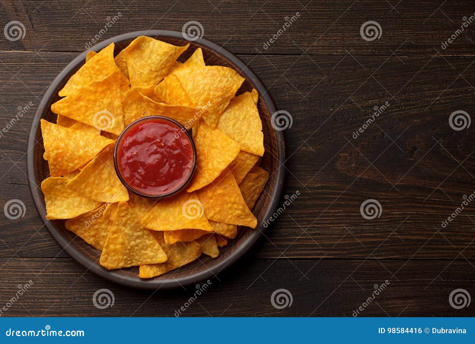 Nachos ou tortilla mexicains de casse-croûte dans le plat d argile avec de la sauce à immersion sur le fond en bois rustique