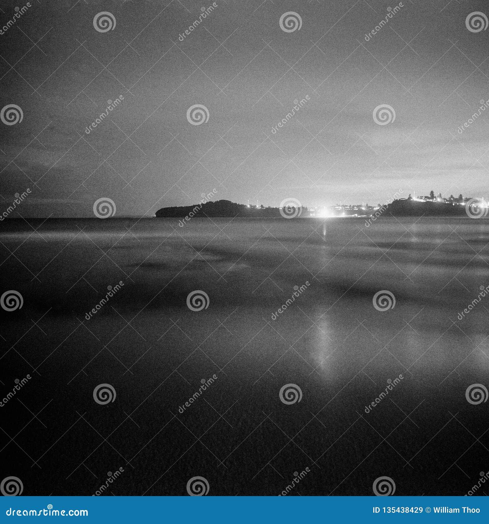 Nacht oceaan lange blootstelling met stadslichten in analo van de het formaat zwart-wit film van afstandsmona vale new south wale
