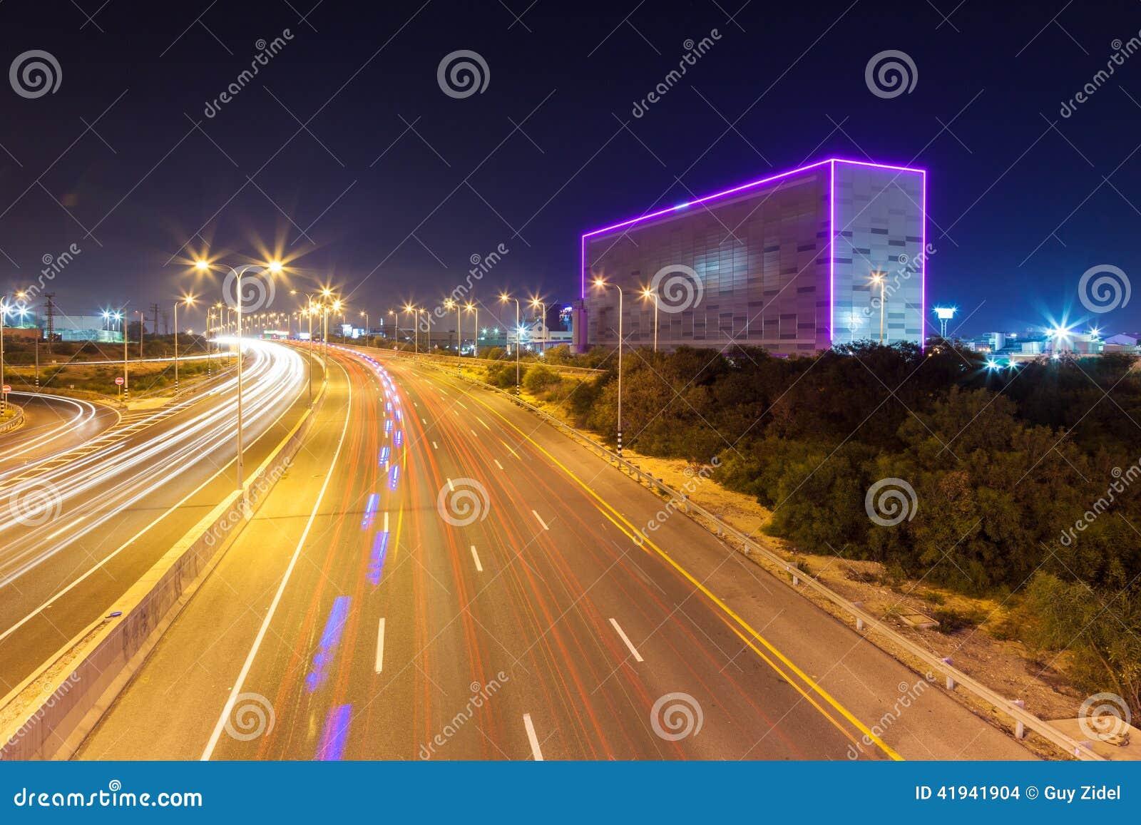 Nachtansicht der Landstraße mit Neonwürfel