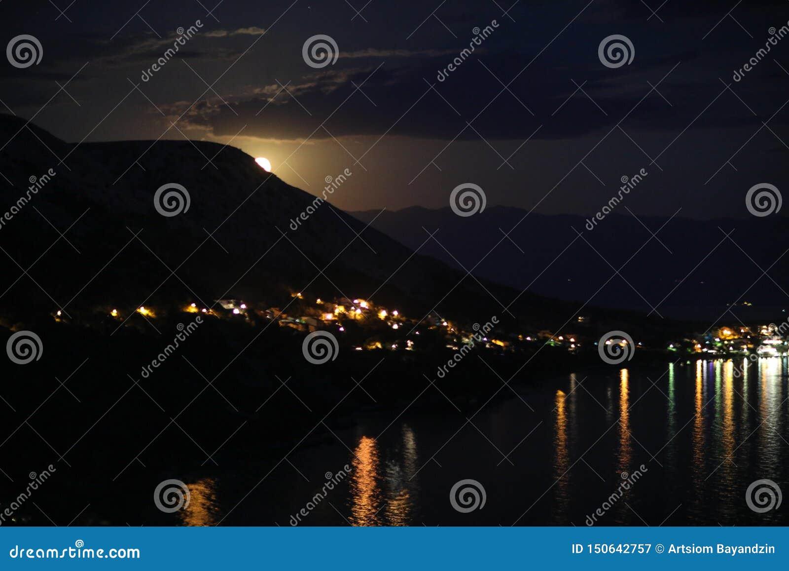 Nachtansicht unter das Mondlicht auf die Stadt auf einem Ufer von adriatischem Meer vom Felshügel in Kroatien, verschiedene Farbt