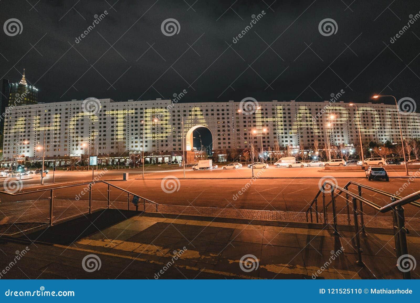 Nachtansicht zum Haus von Ministerien mit Werbung für den 9. Mai in Astana, Kasachstan