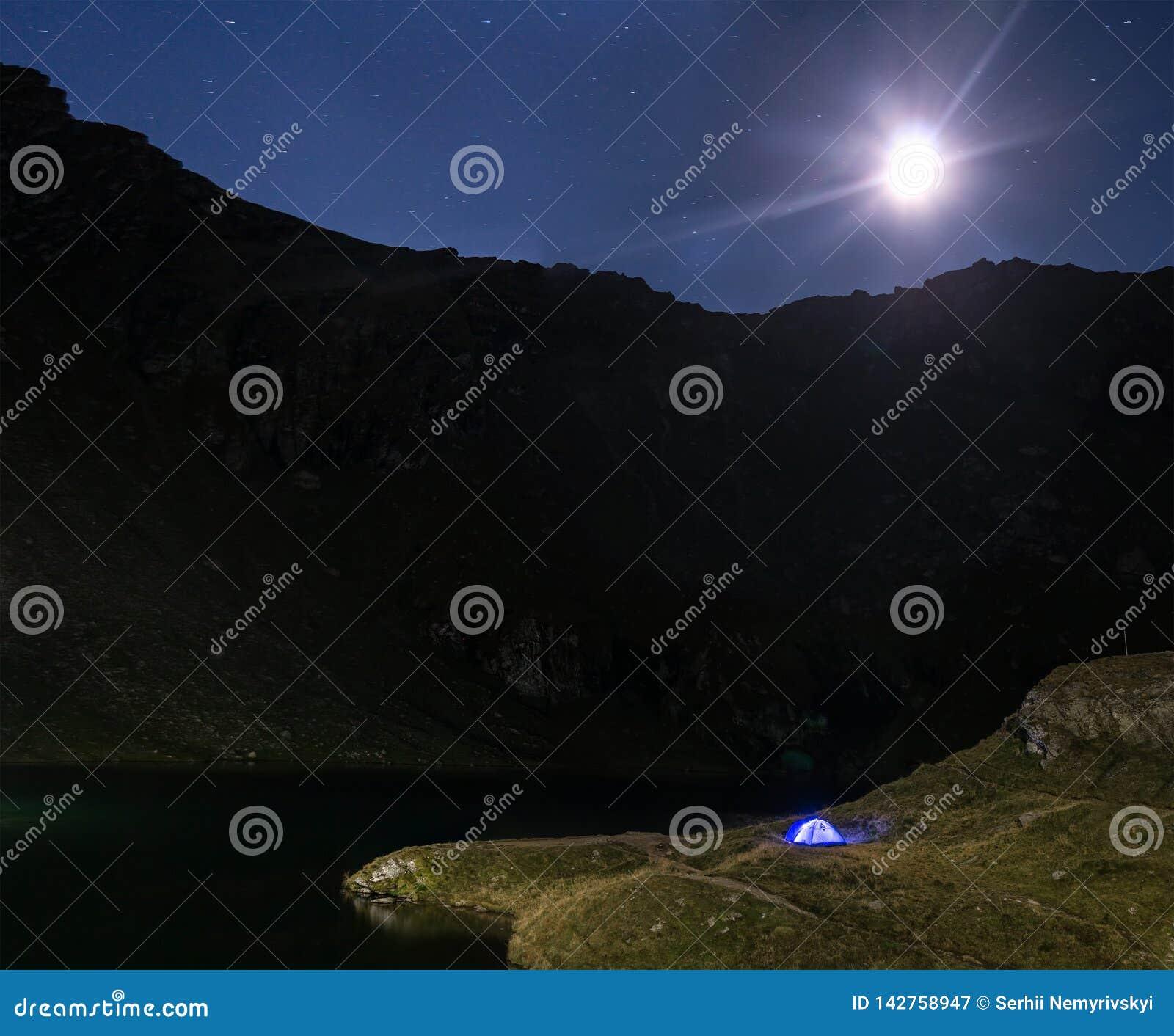 Nachtberglandschaft mit belichtetem blauem Zelt Bergspitzen und der Mond im Freien Lacul Balea am See, Transfagarasan,