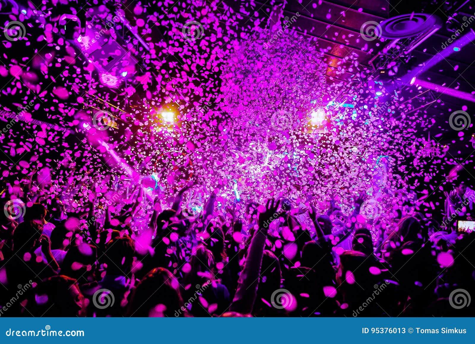 Nachtclub-Schattenbildmenge übergibt oben in Konfettidampfstadium