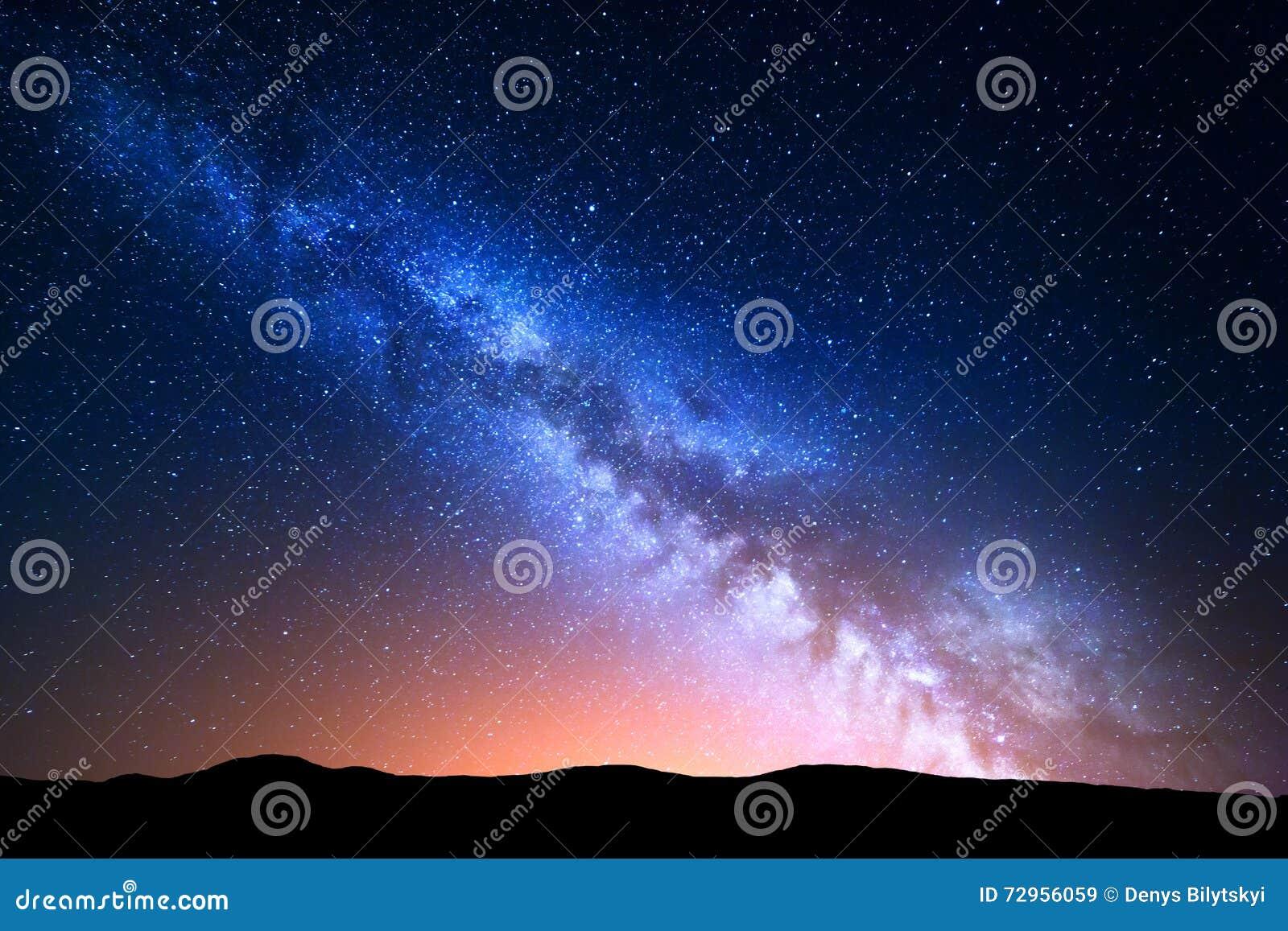 Nachtlandschap met kleurrijke Melkweg en geel licht bij bergen Sterrige hemel met heuvels bij de zomer Mooi Heelal ruimte