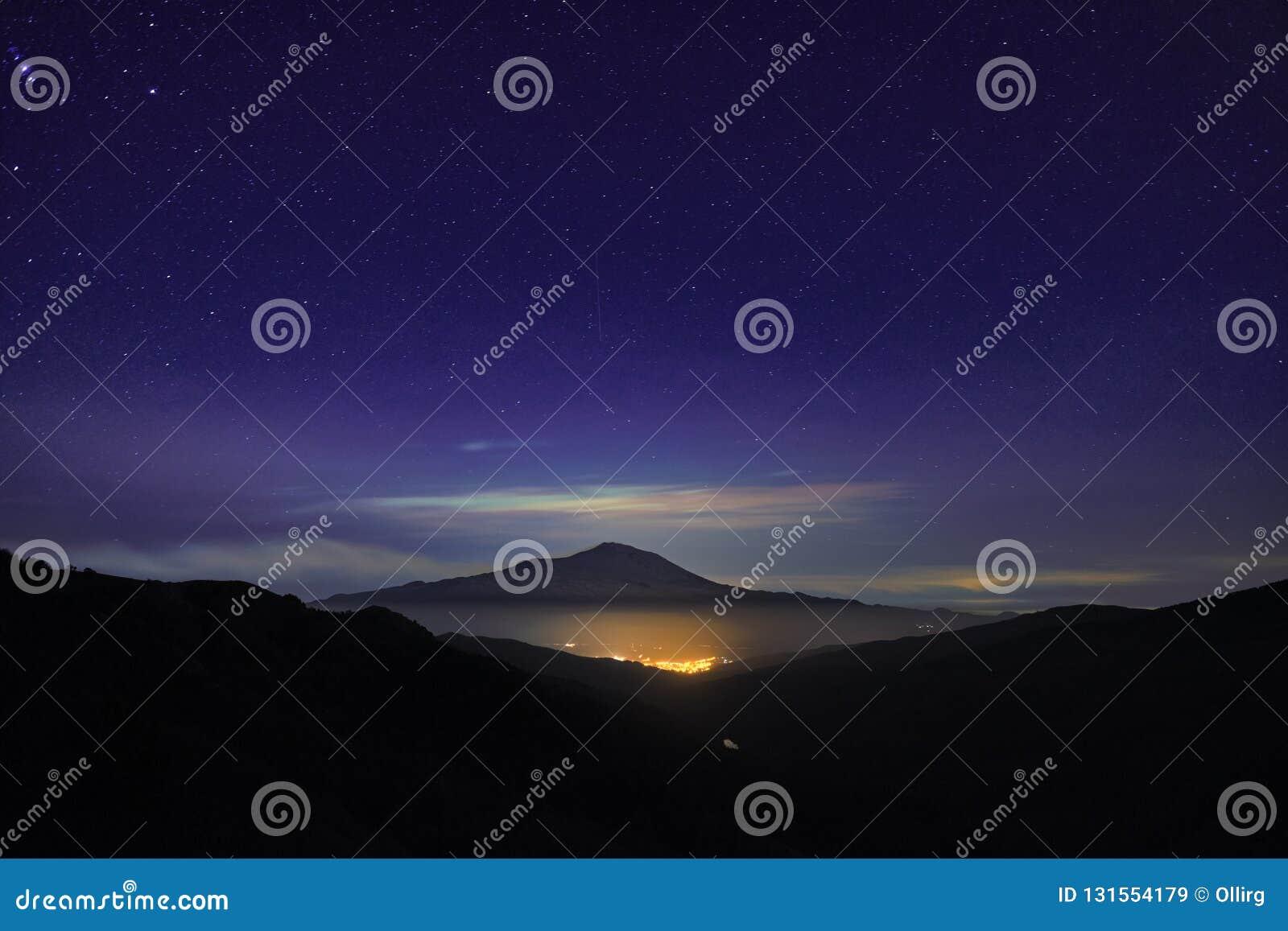 Nachtlicht von Randazzo-Stadt voll glühend unter Etna Mount und Himmel von Sternen von Nebrodi-Park