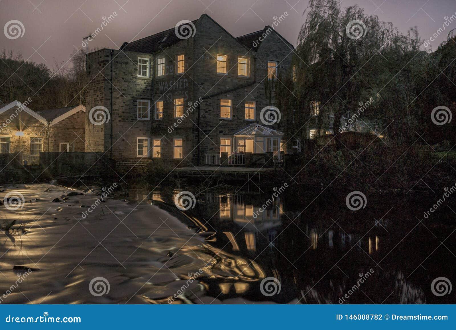 Nachtmening van een oude die molen in de rivier wordt weerspiegeld