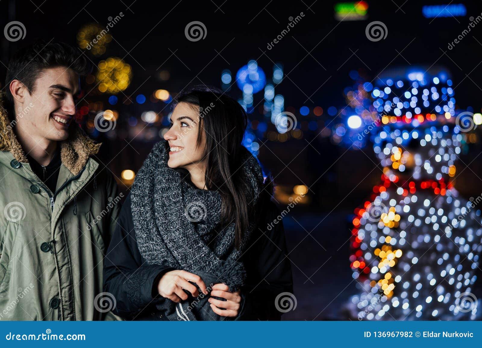Nachtportret van een gelukkig paar die genietend de winter en sneeuw van aoutdoors glimlachen De wintervreugde Positieve emoties