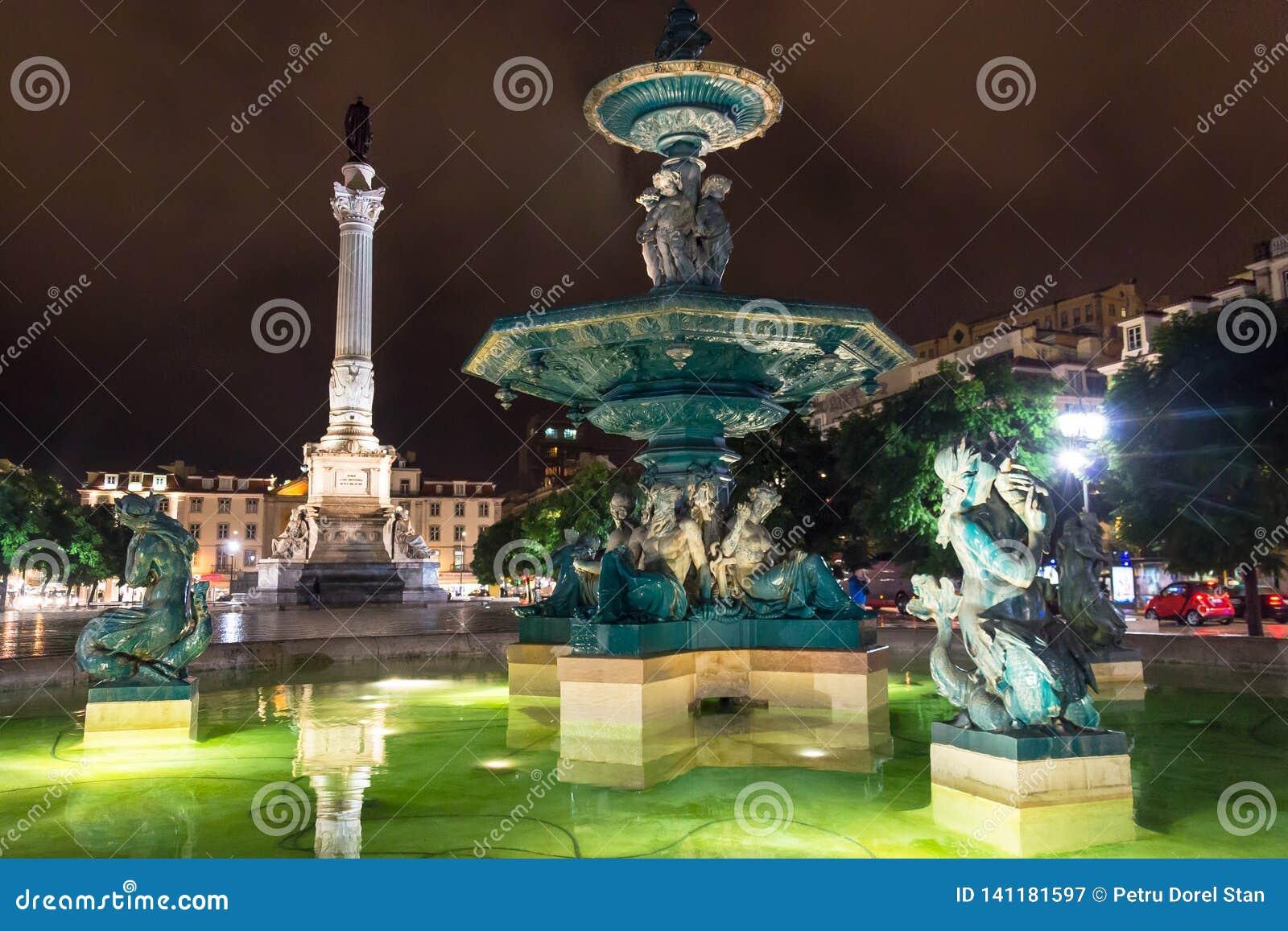Nachtscène van Rossio-Vierkant, Lissabon, Portugal met één van zijn decoratieve fonteinen en de Kolom van Pedro IV