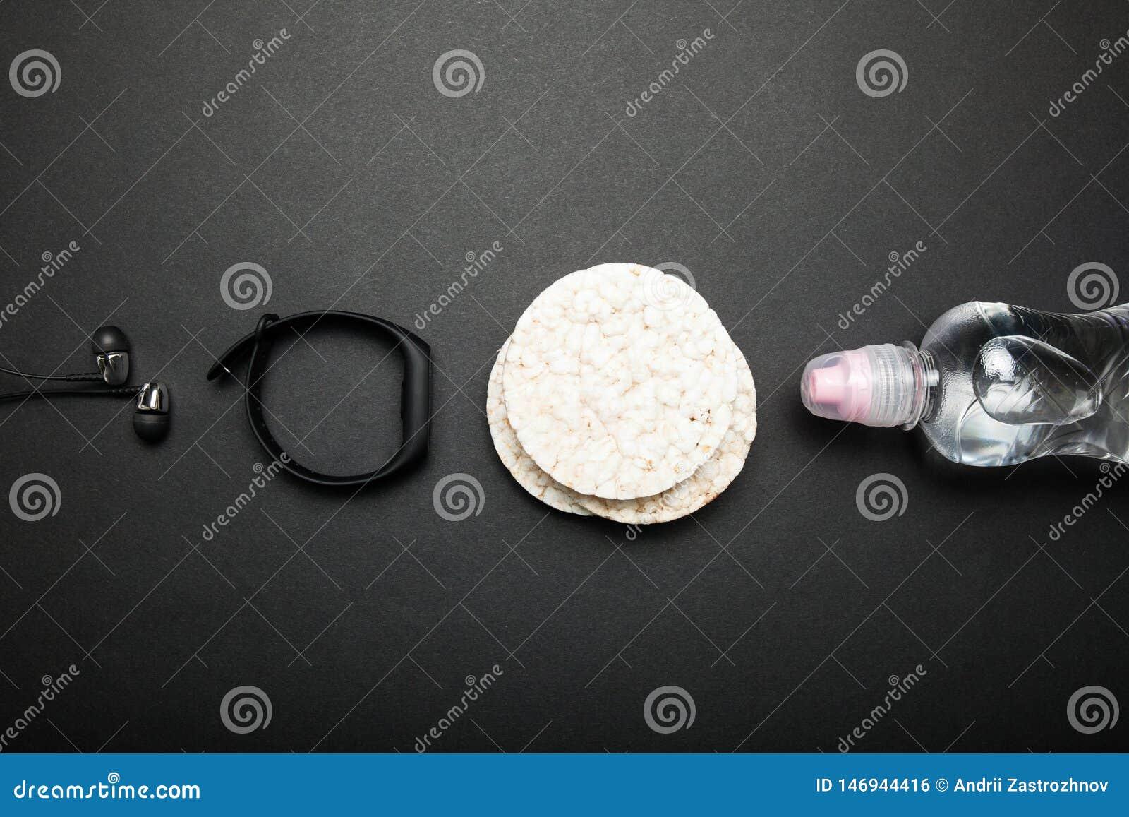 Naco dietético do arroz, garrafa da água, bracelete da aptidão e fones de ouvido em um fundo preto