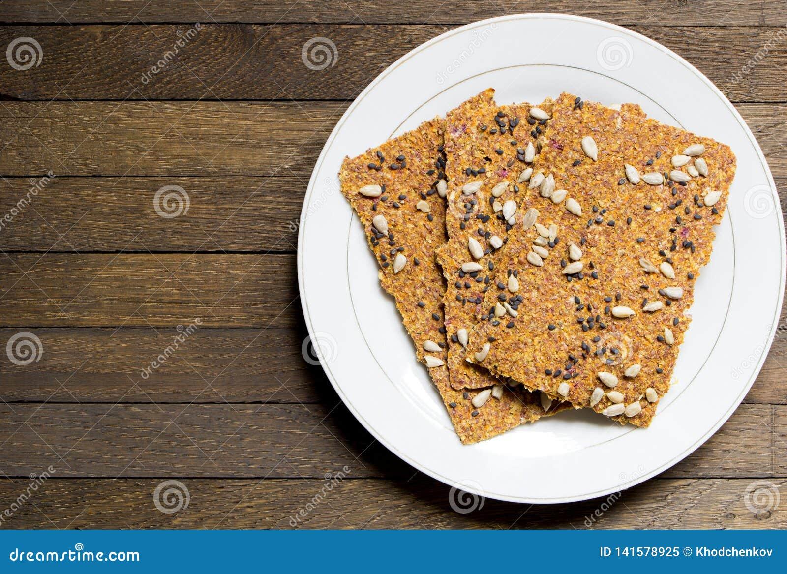 Nacos crus desidratados vegetariano do pão no prato branco na tabela de madeira