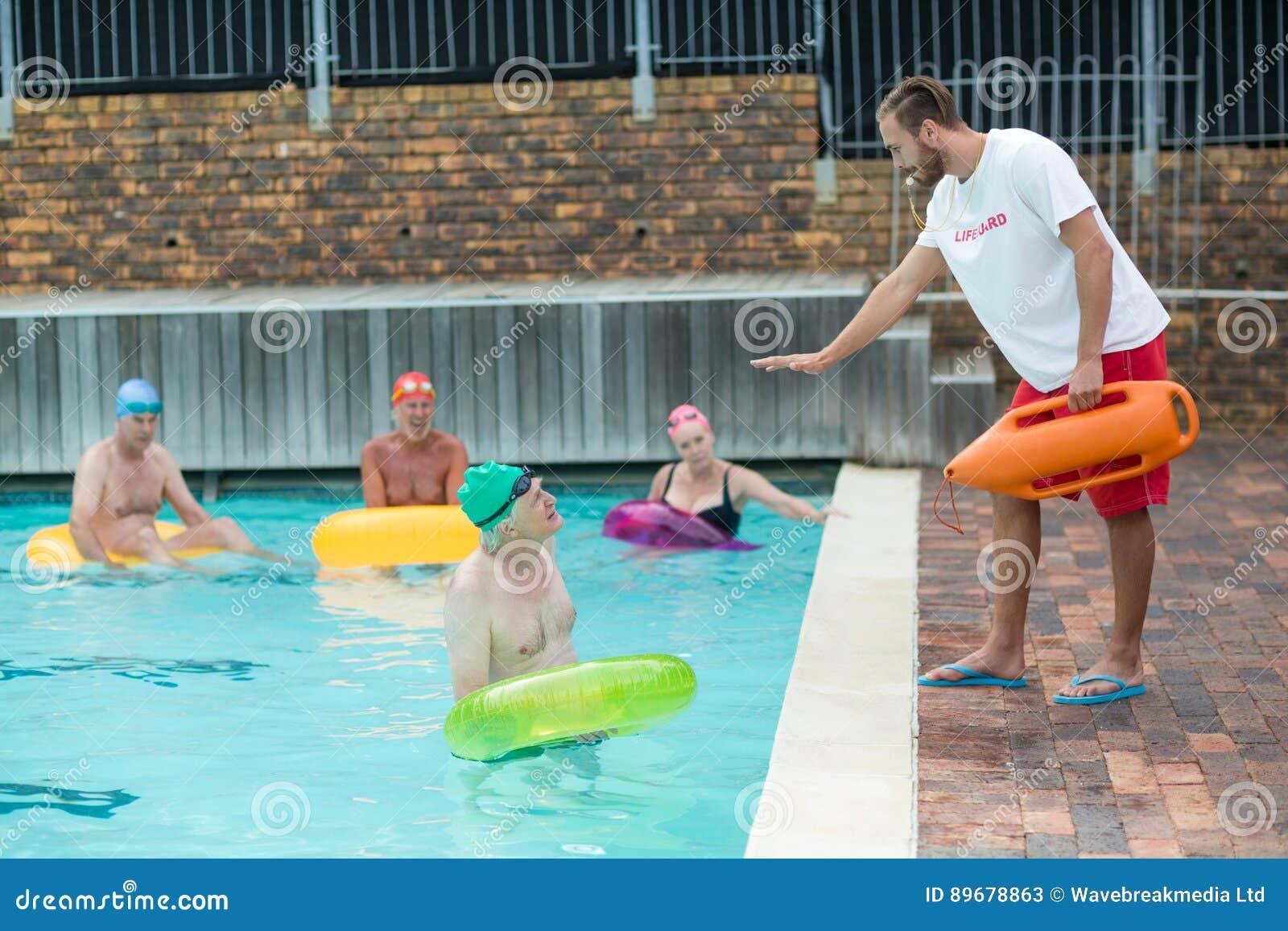Nadadores de ayuda del salvavidas en el poolside