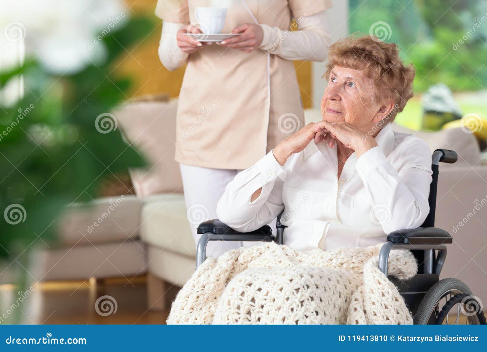 Nadenkend verlamd bejaarde in een rolstoel en haar careg