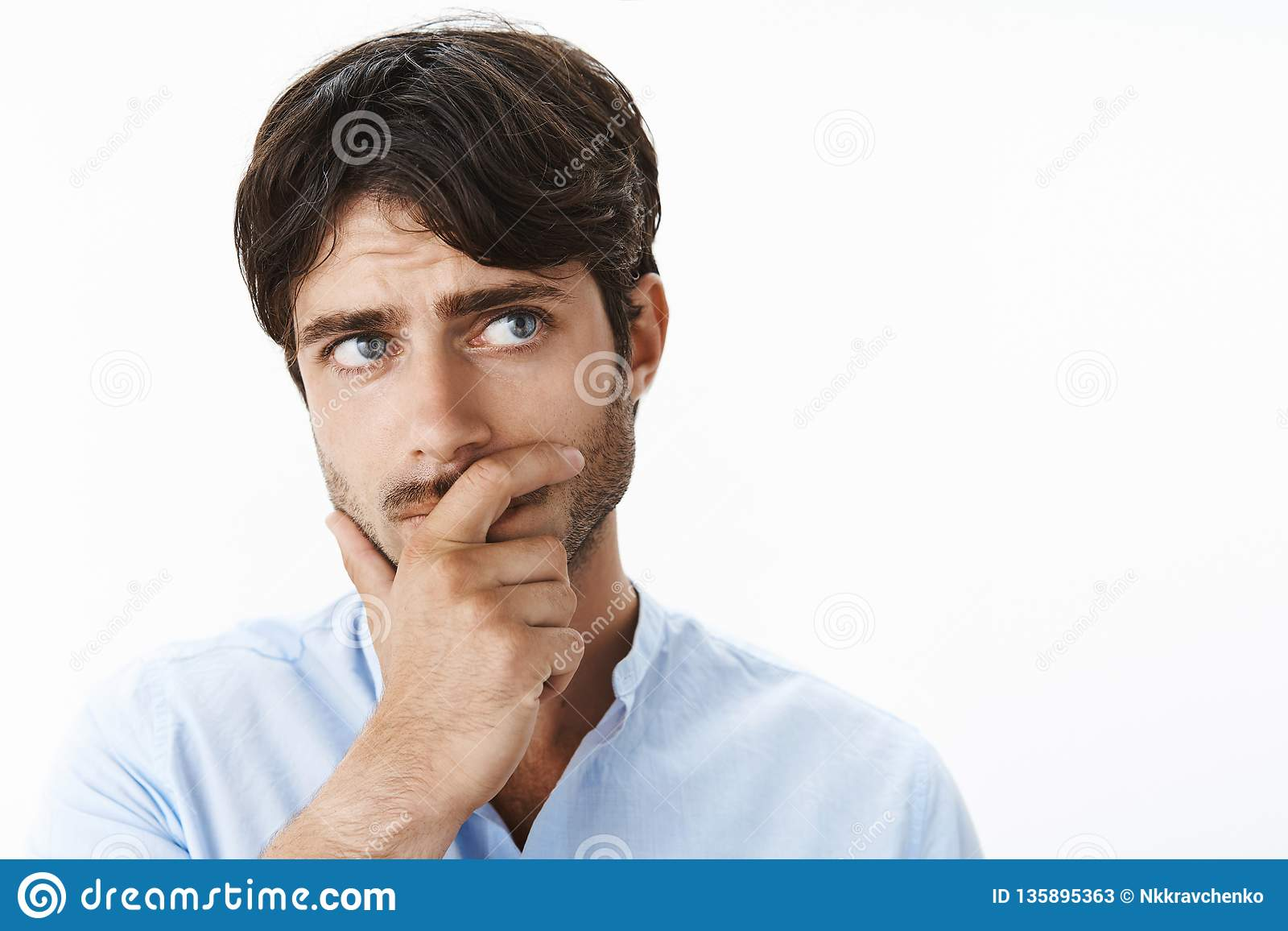 Nadenkende betrokken jonge ondernemer met diepe blauwe ogen en de hand van de varkenshaarholding op kaak die hoger recht bekijken