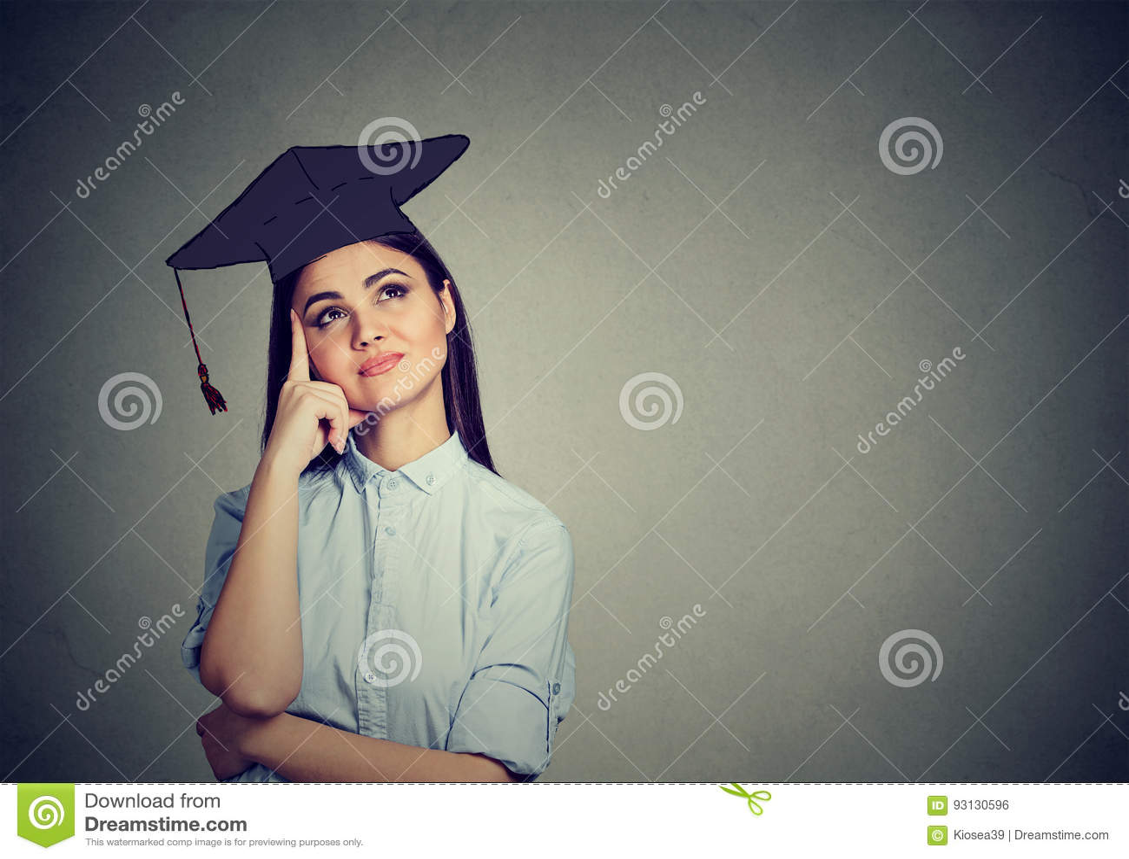 Nadenkende gediplomeerde studentenvrouw die in GLB-toga omhoog denkend kijken