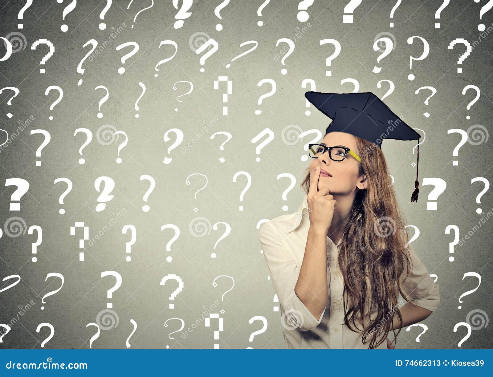 Nadenkende gediplomeerde studentenvrouw met vele vraagtekens boven hoofd