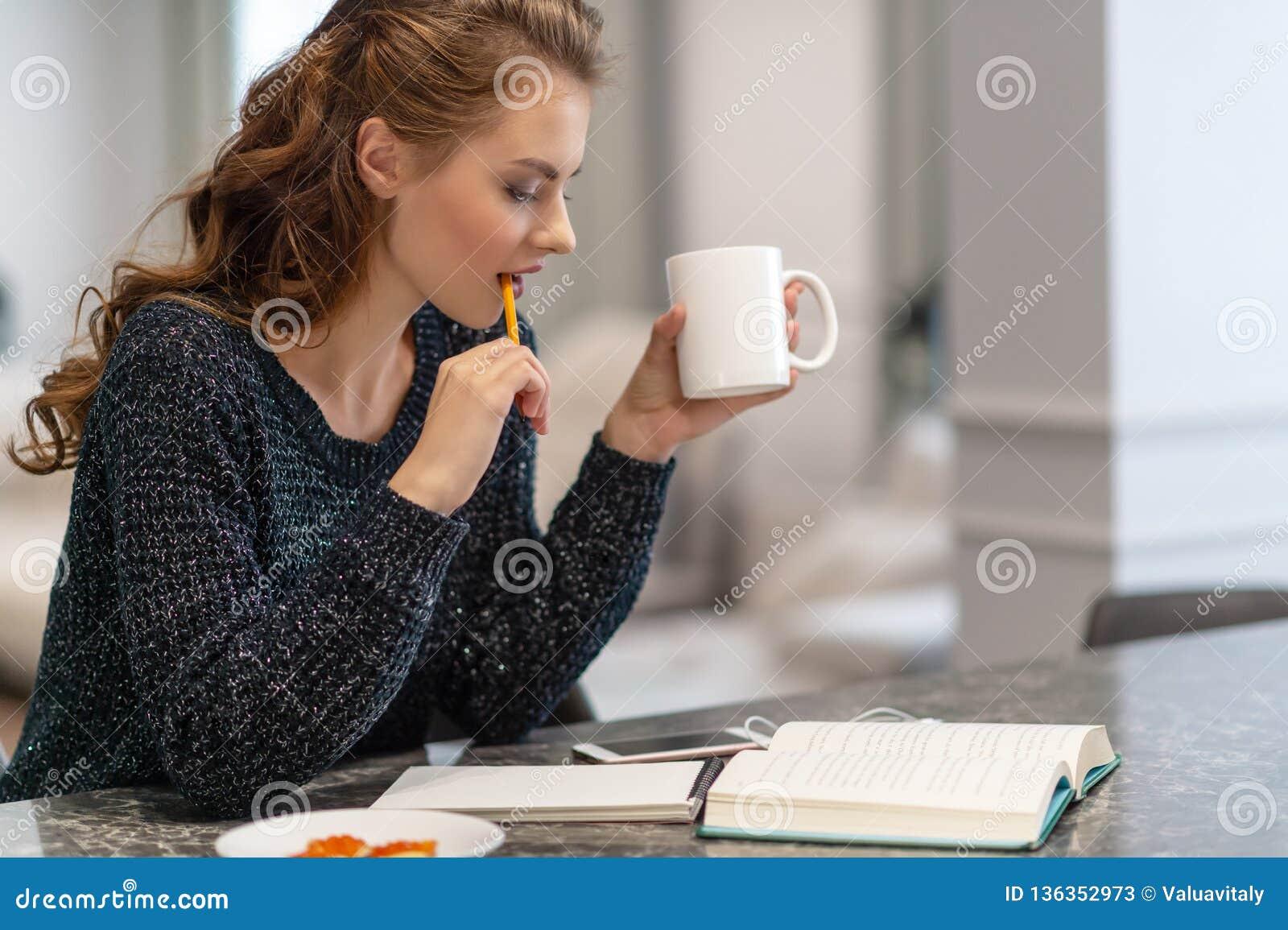Nadenkende jonge vrouw die nota s maken die blocnote in keuken gebruiken