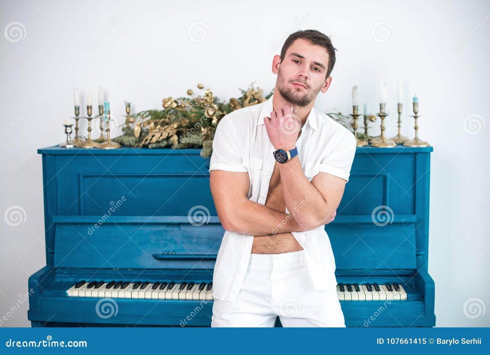 Nadenkende, knappe mens met een baard in witte kleren tegen de achtergrond van een piano, een geraspt overhemd met een naakt tors