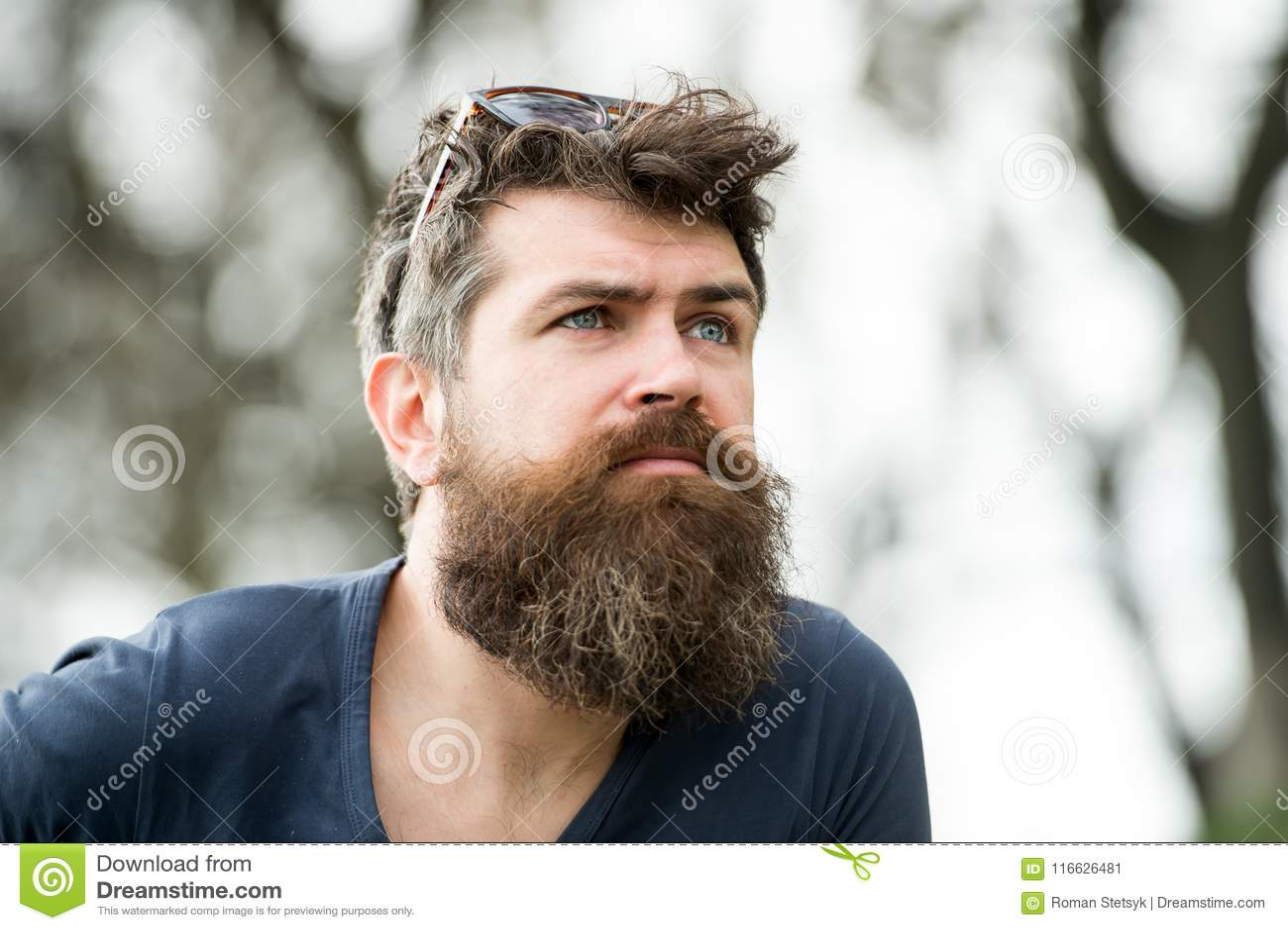 Nadenkende mens die met blauwe ogen het hemel, kalmte en mindfulnessconcept onderzoeken Jonge gebaarde hipster met
