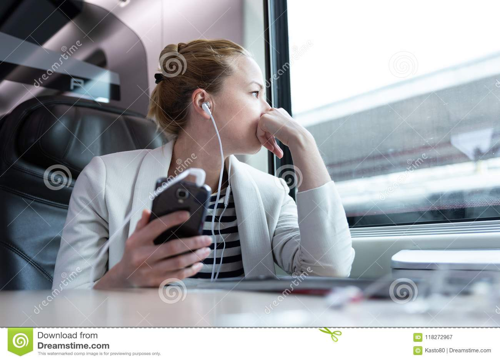 Nadenkende onderneemster die aan podcast op mobiele telefoon luisteren terwijl het reizen door trein