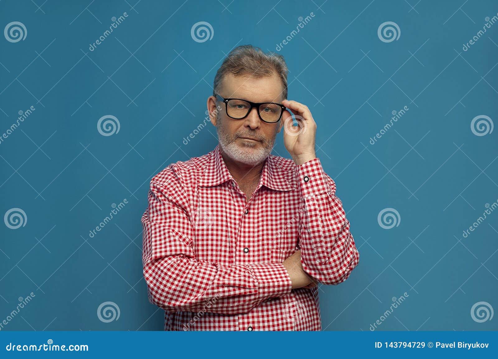 Nadenkende oude mens die slim toevallig overhemd en modieuze glazen dragen