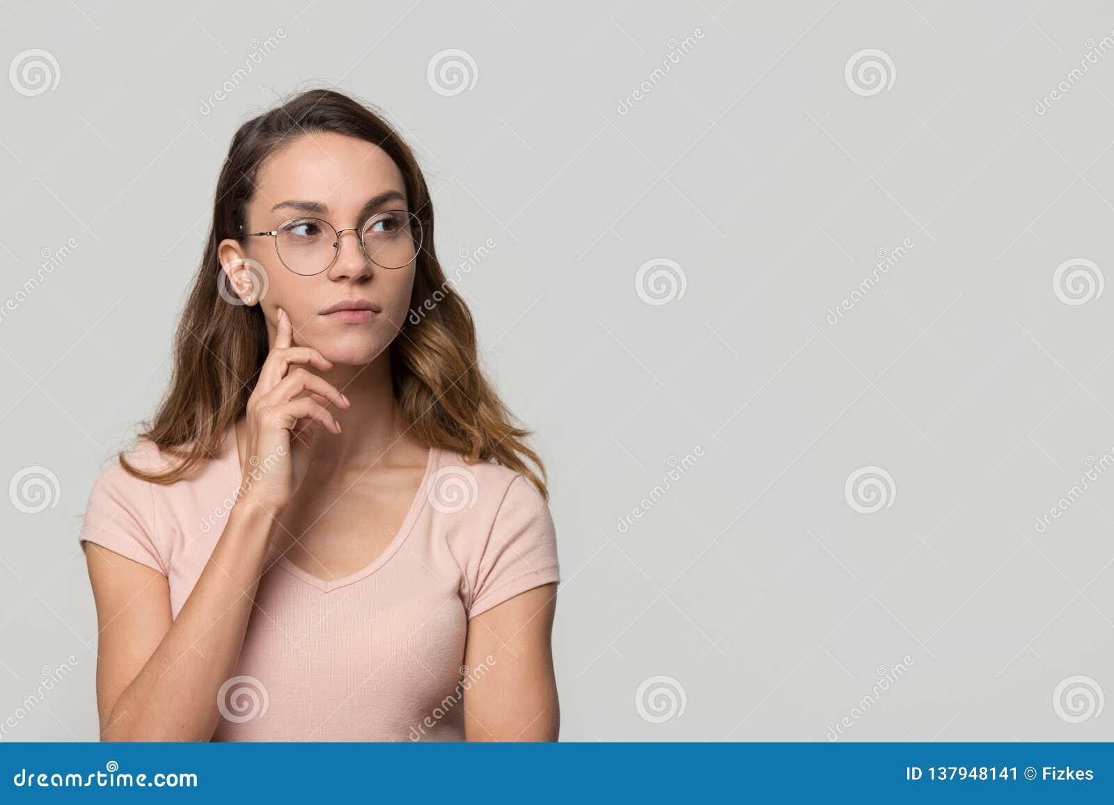Nadenkende twijfelachtige vrouw die onzekere copyspace bekijken geïsoleerd op achtergrond