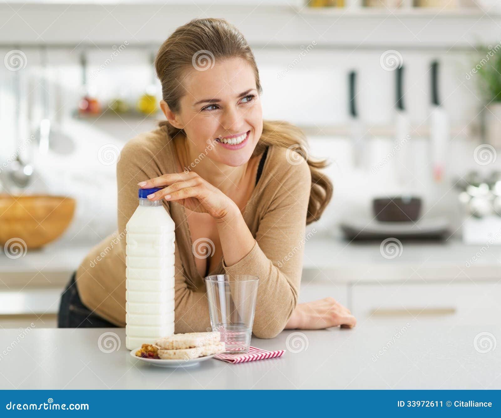 Nadenkende vrouw met kernachtig brood en melk in keuken