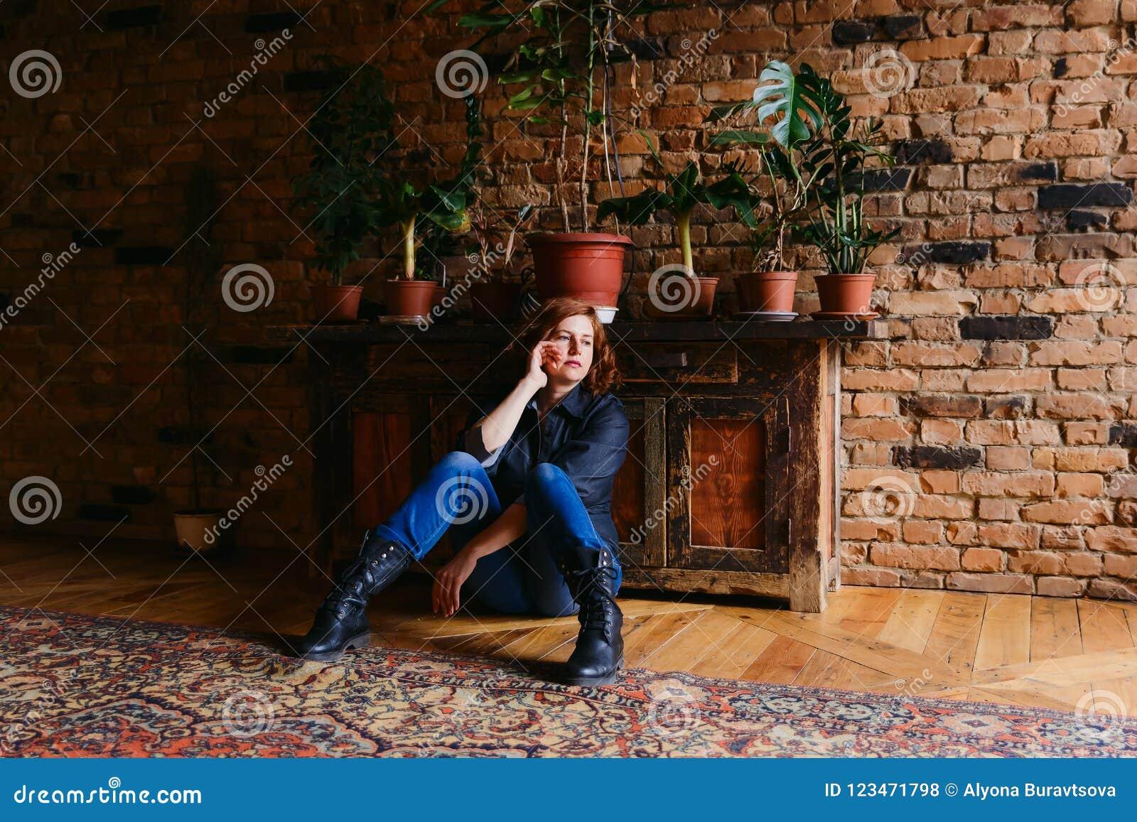 Nadenkende vrouwenzitting op middelbare leeftijd op de vloer