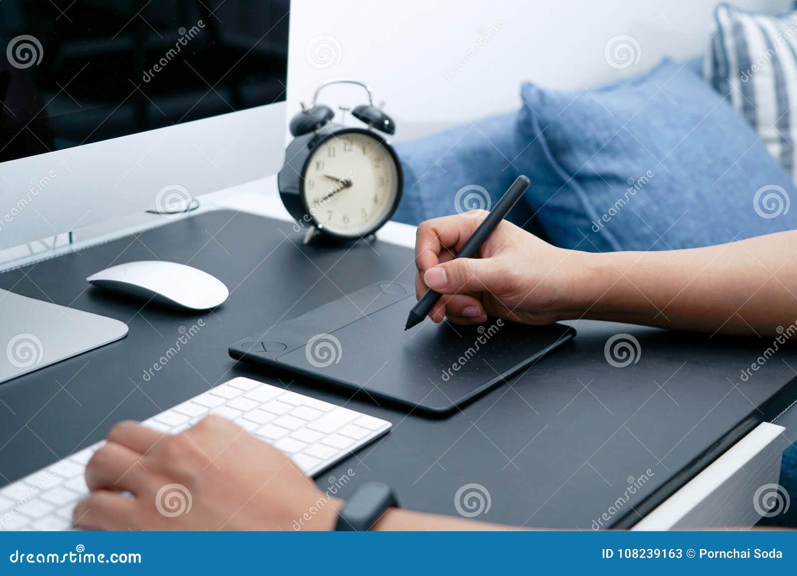 Nadruk op de bezige grafische ontwerper die aan computer door digitale penmuis werken