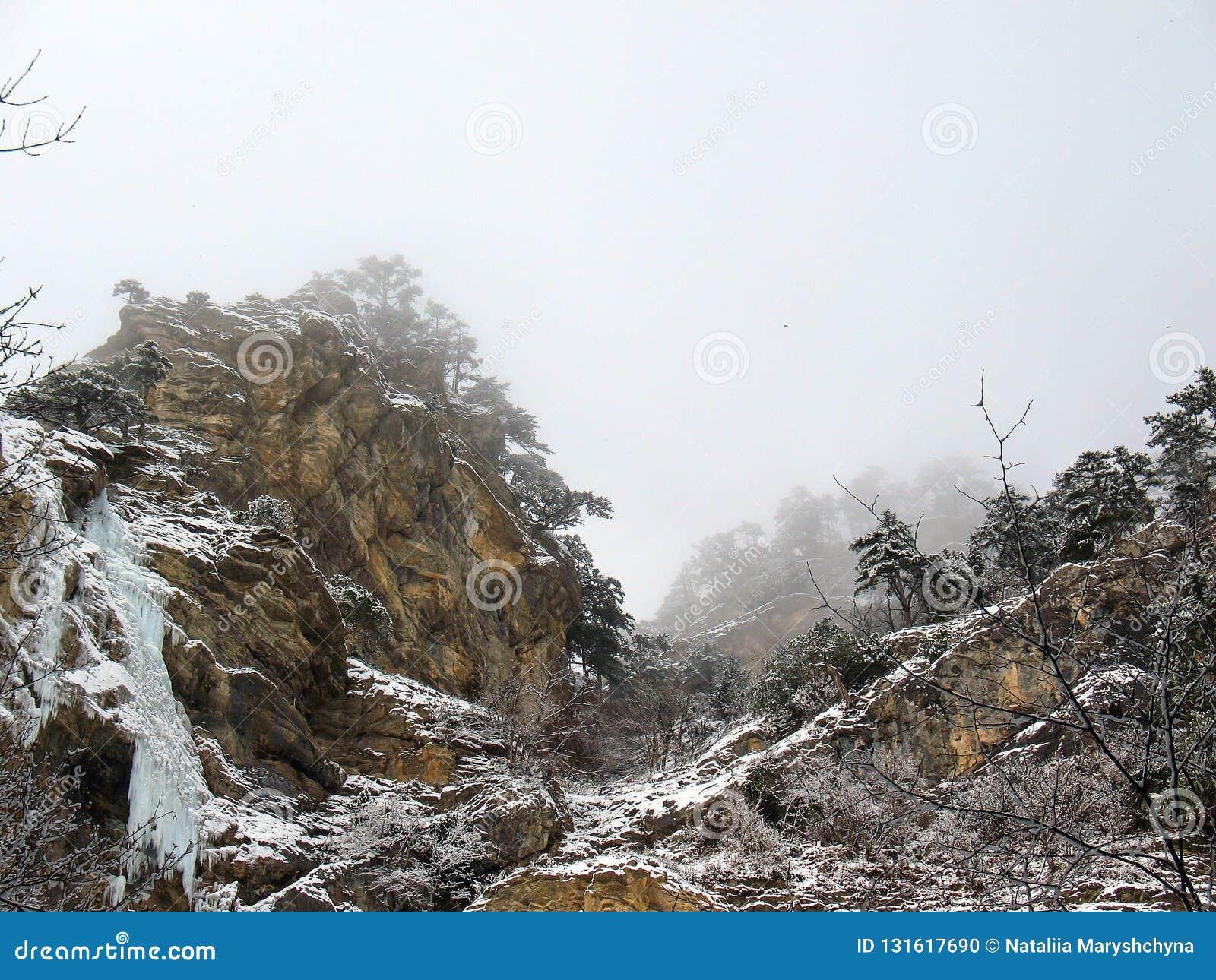 Nadzwyczajny pomarańczowy śnieg zakrywać skały wodospad mrożone Spadać kaskadą góry z drzewami chuje w mgle