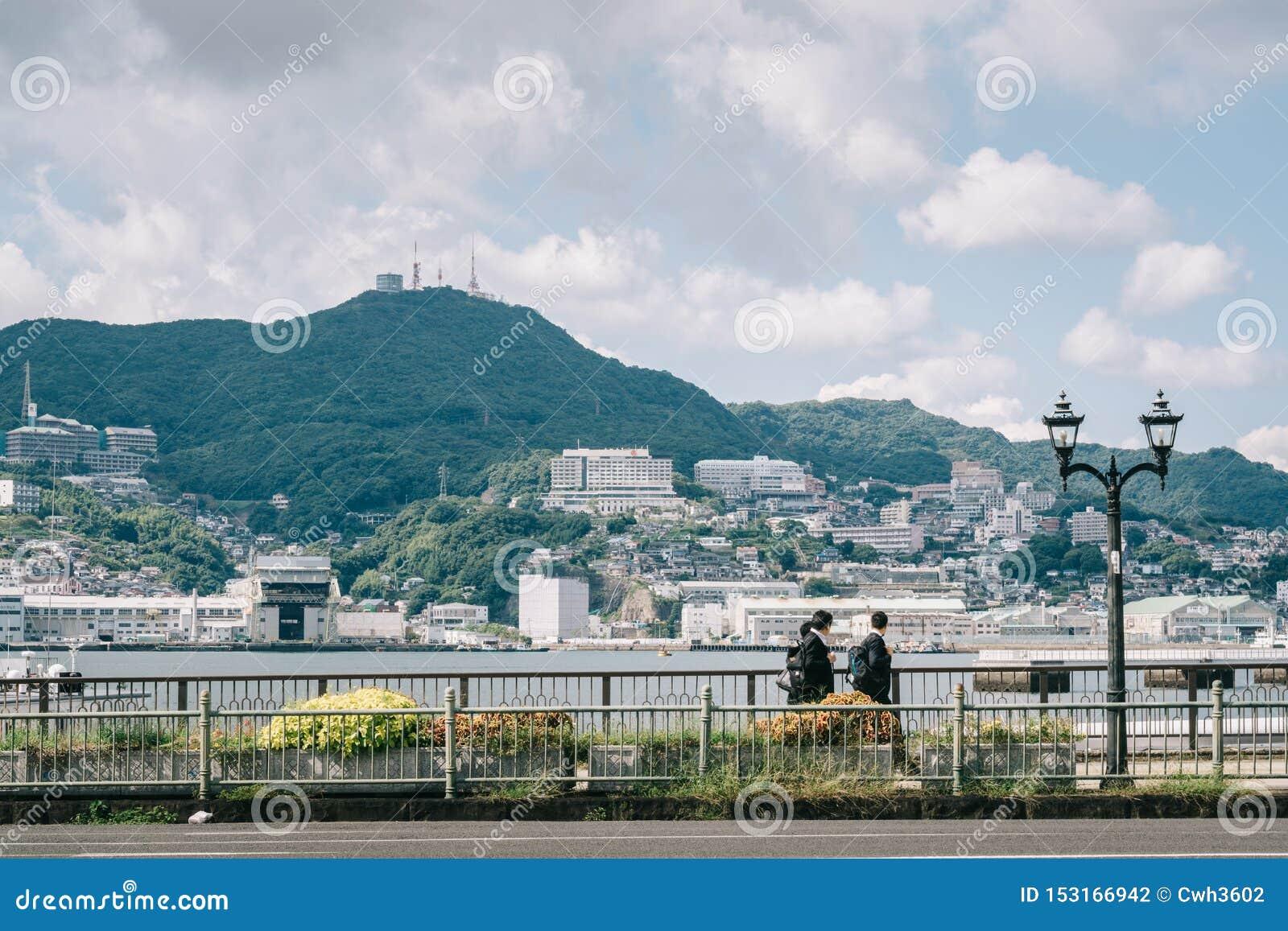 Nagasaki, Kyushu, Japón, el Este de Asia - estudiantes que van a casa después de escuela en un fondo del paisaje hermoso con el m