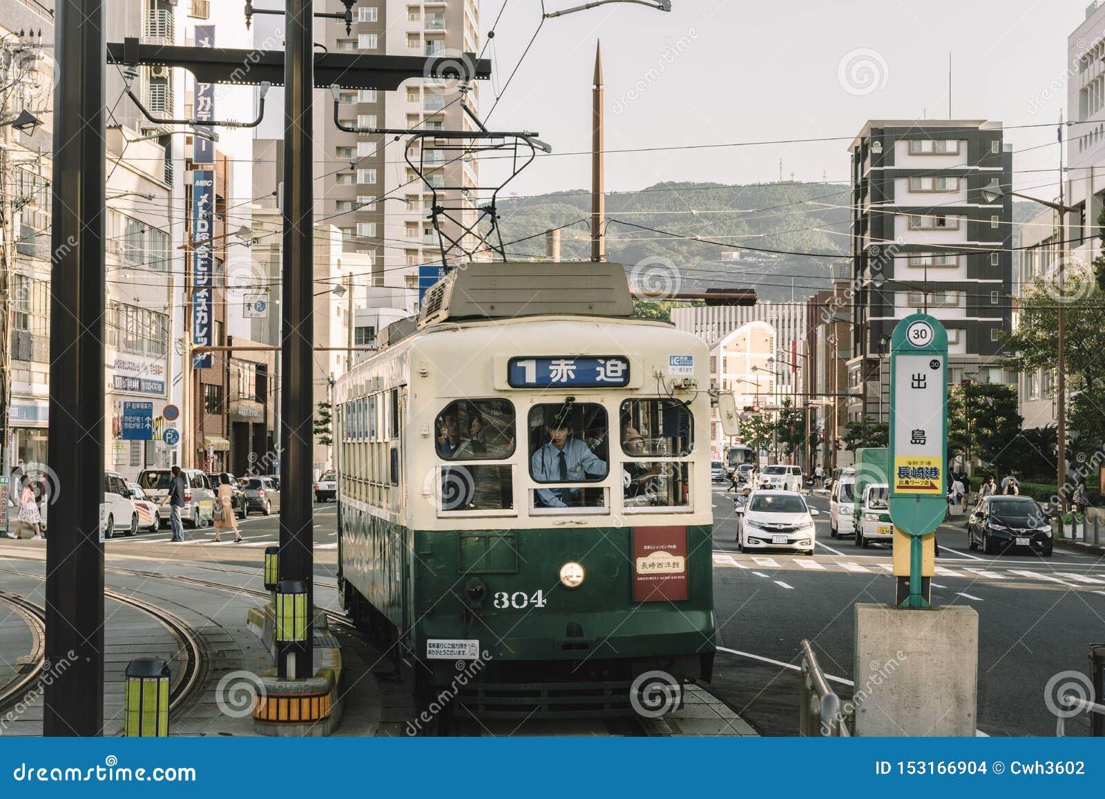 Nagasaki, Kyushu, Japan, Oost-Azië - 7 Oct 2017: Een oude overvolle tram die in het platform komt