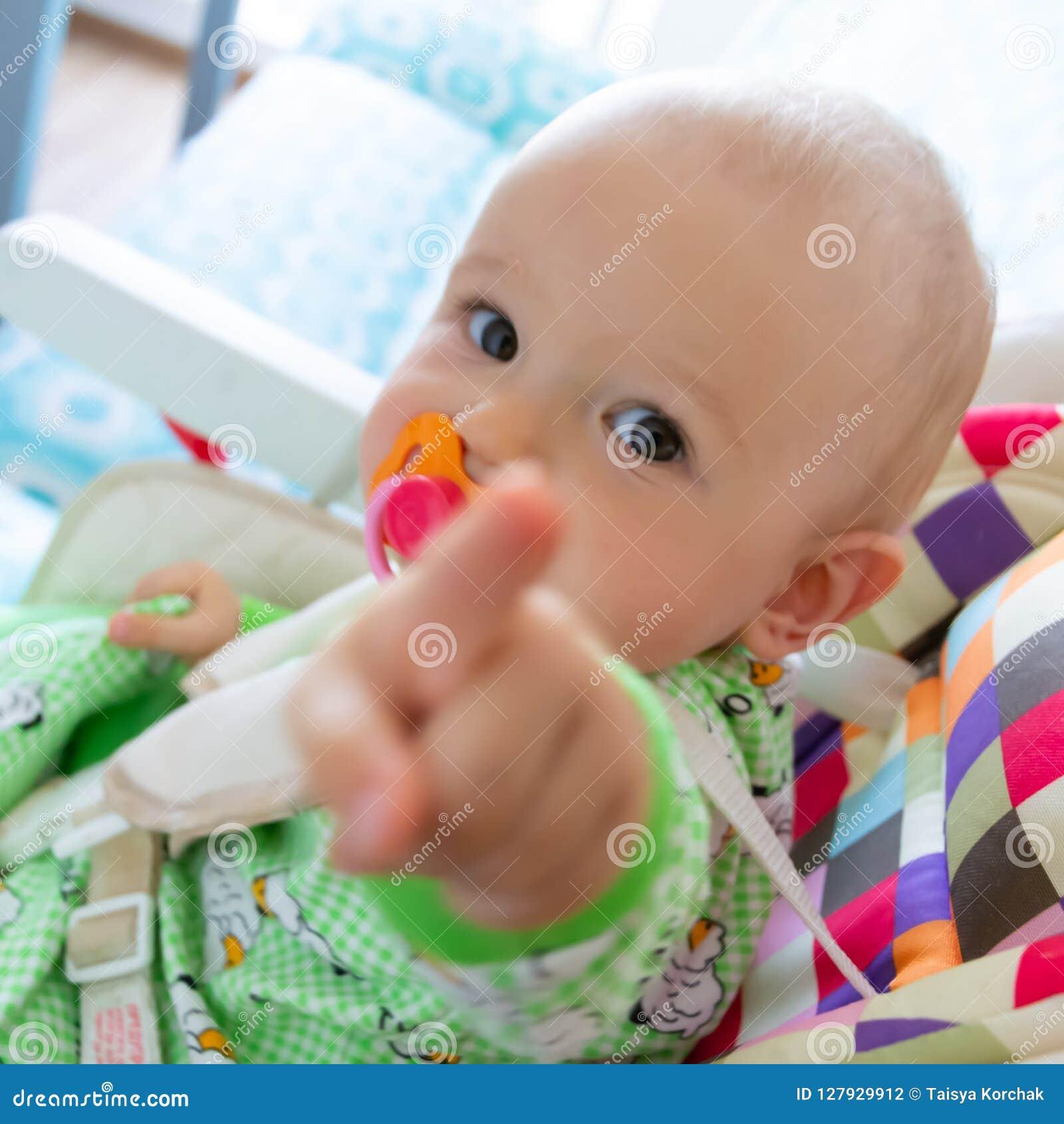 Nagen mit einen saugt das jährige Babys/auf einem Gumminippel, weil seine Zähne geschnitten werden Kleiner netter Junge in eine h
