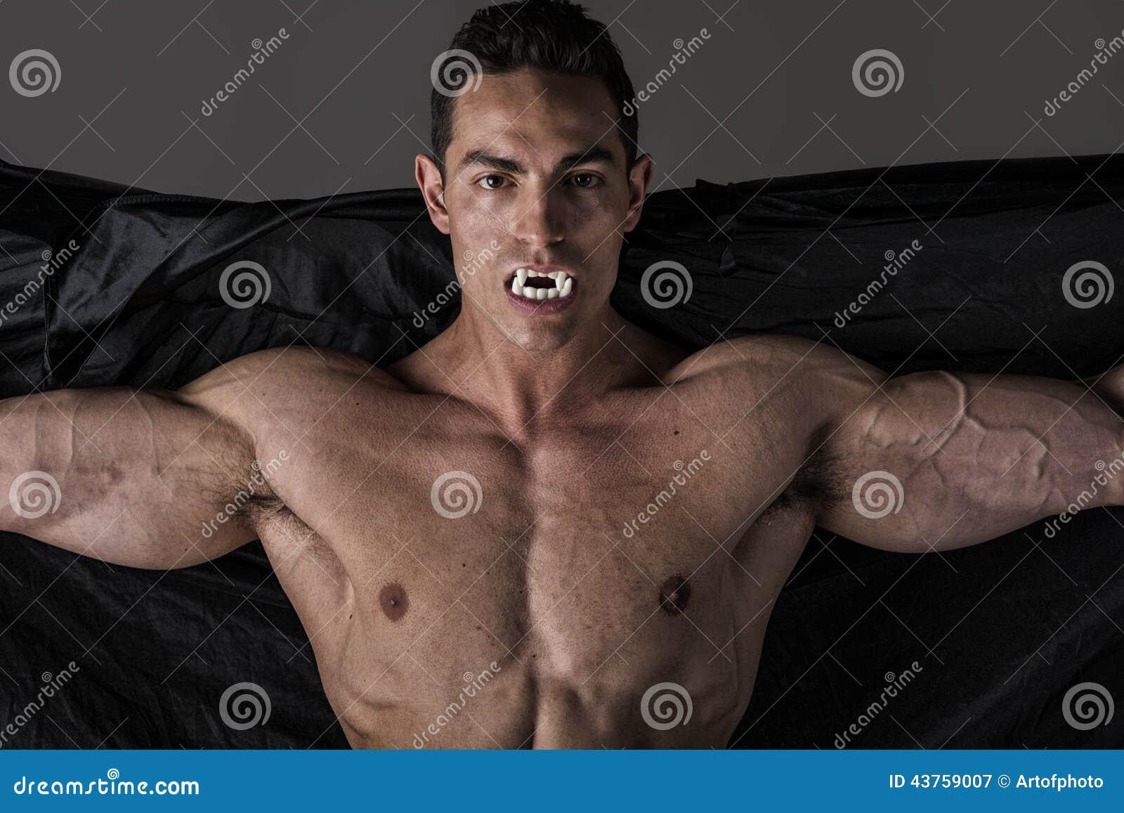 Nagi mięśniowy dysponowany młody człowiek w wytyczne pozuje jako Dracula lub wampir