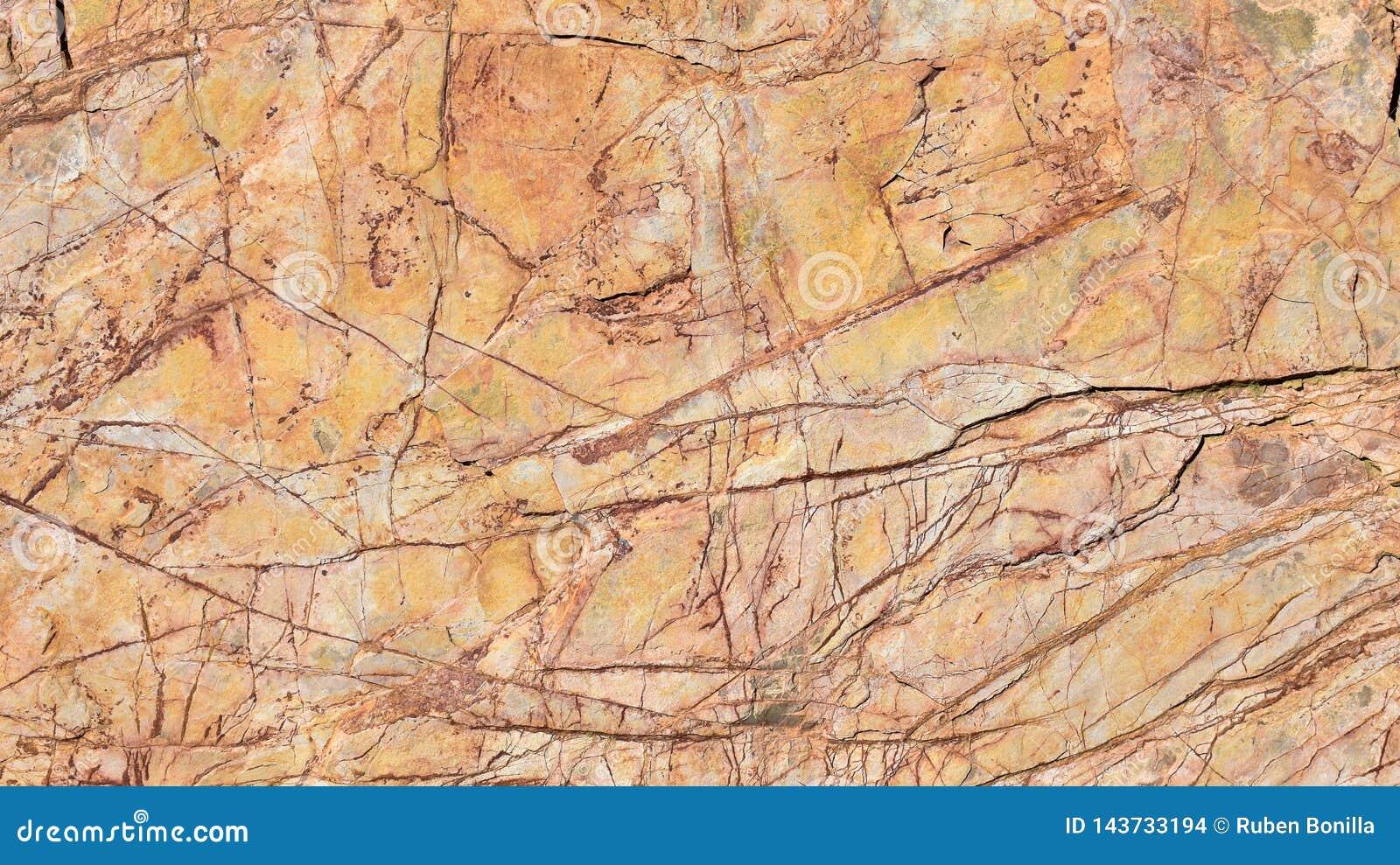 Nah oben von einem verkratzten alten orange Stein einer Architekturwand, die den Innenraum eines Hauses verziert Horizontales Fot