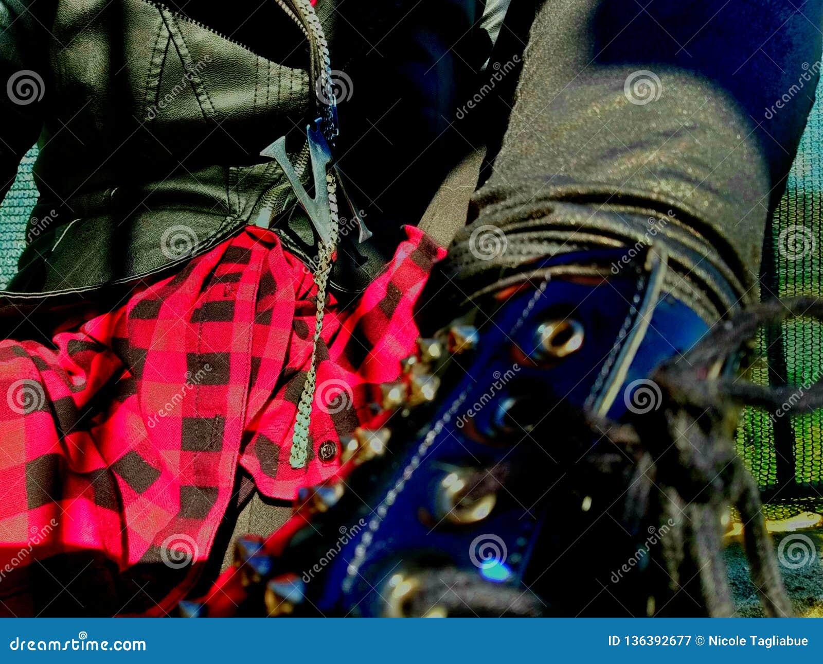 Nahaufnahme auf bezaubernden Artdetails des punk rock, Stoffe und Zusätze - Mädchenstiefel, rotes Hemd und schwarze Lederjacke