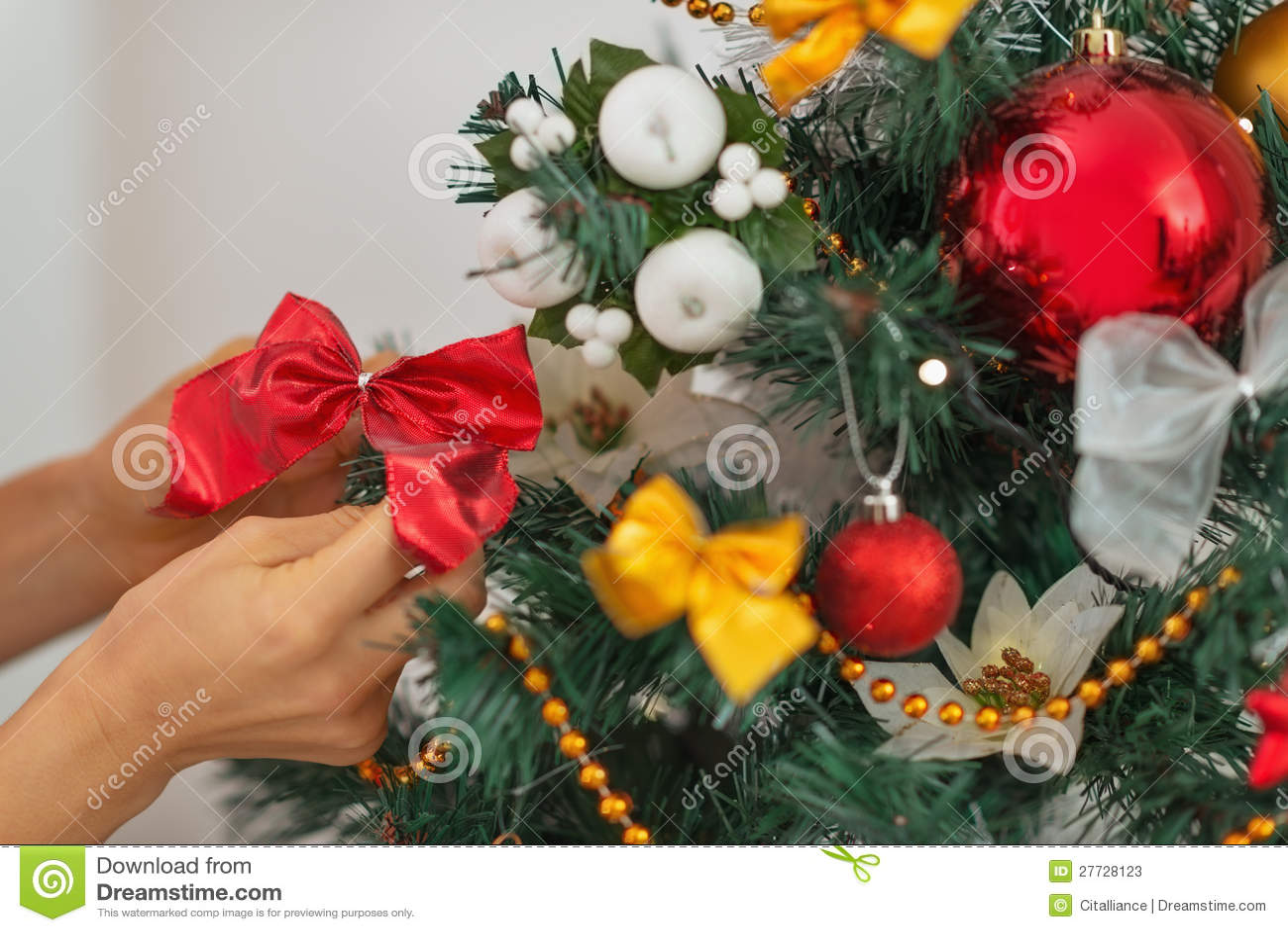 Nahaufnahme auf der Frauenhand, die Weihnachtsbaum verziert