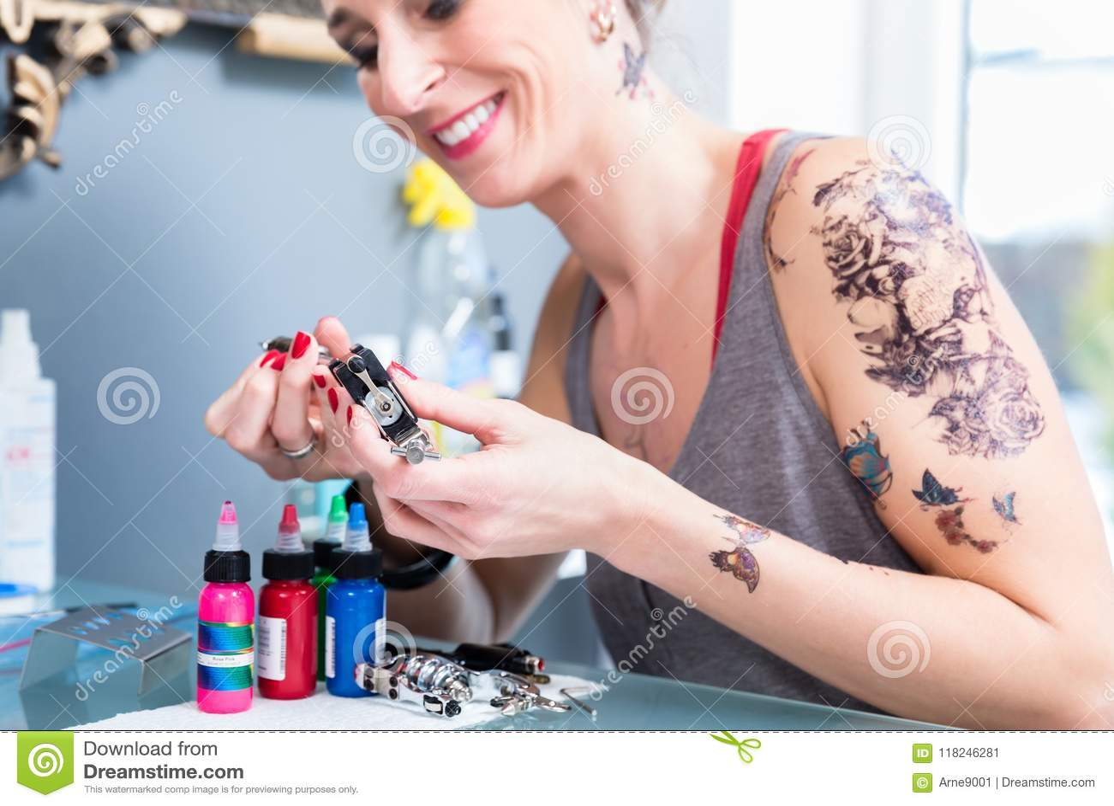 Nahaufnahme der Hände eines weiblichen Künstlers, der eine Berufstätowierungsmaschine vorbereitet