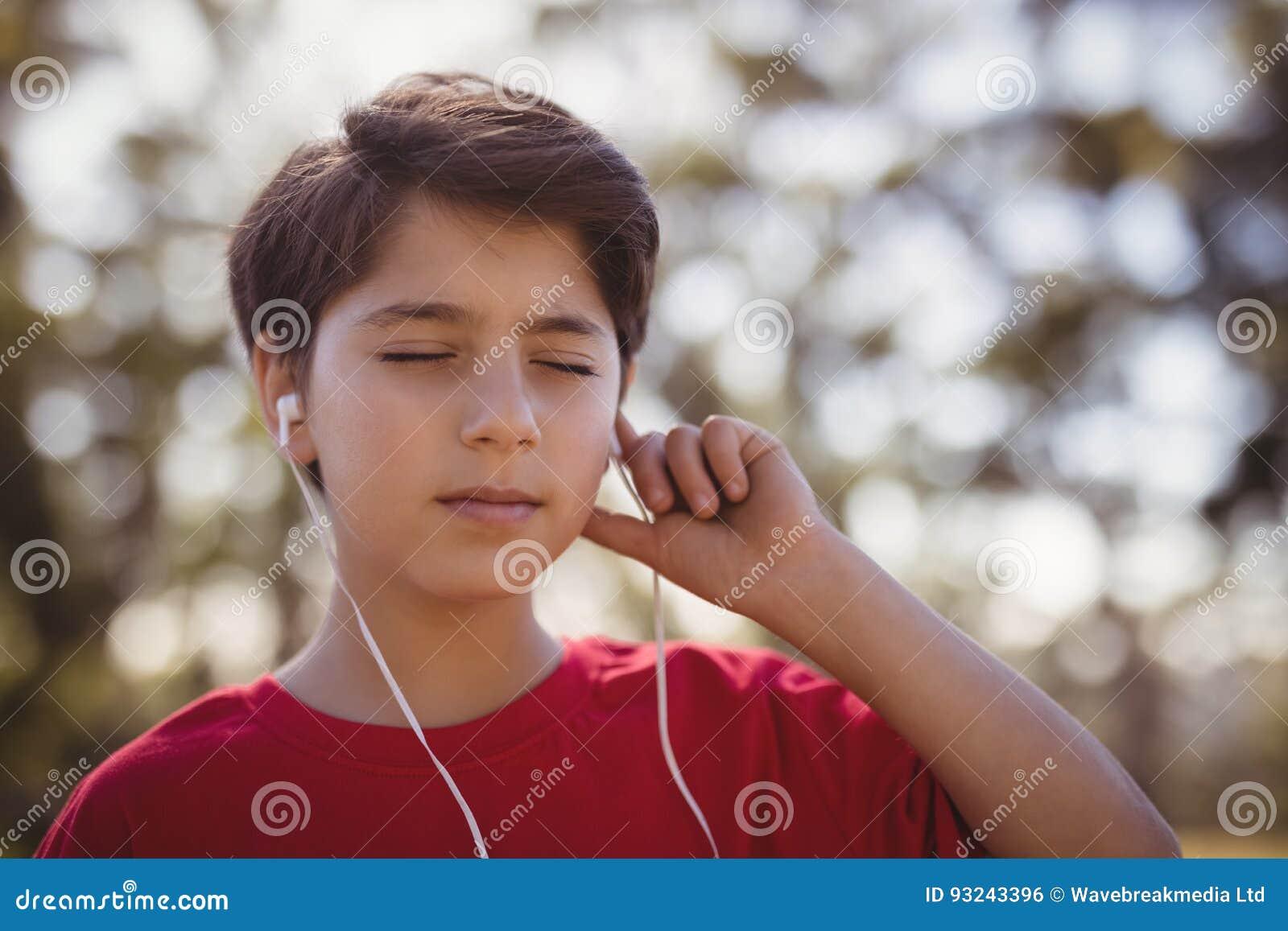 Nahaufnahme der hörenden Musik des Jungen auf Kopfhörern während des Hindernislaufs