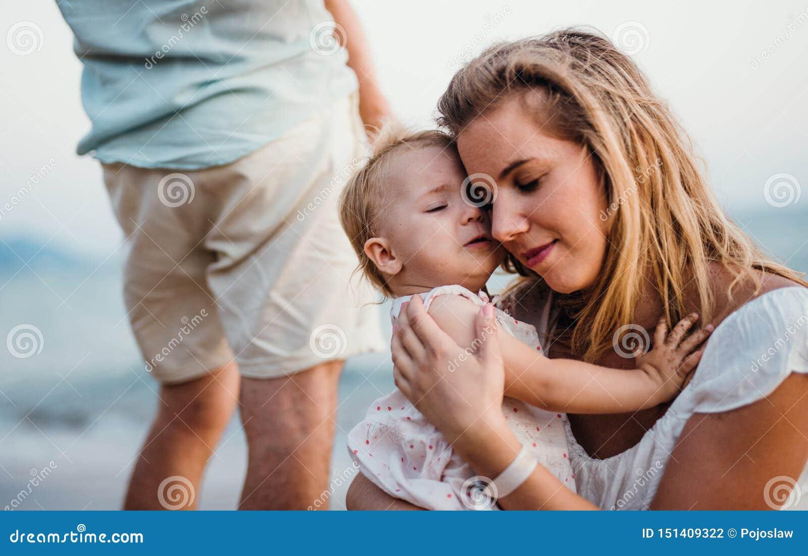 Nahaufnahme der jungen Mutter mit einem Kleinkindm?dchen auf Strand an den Sommerferien