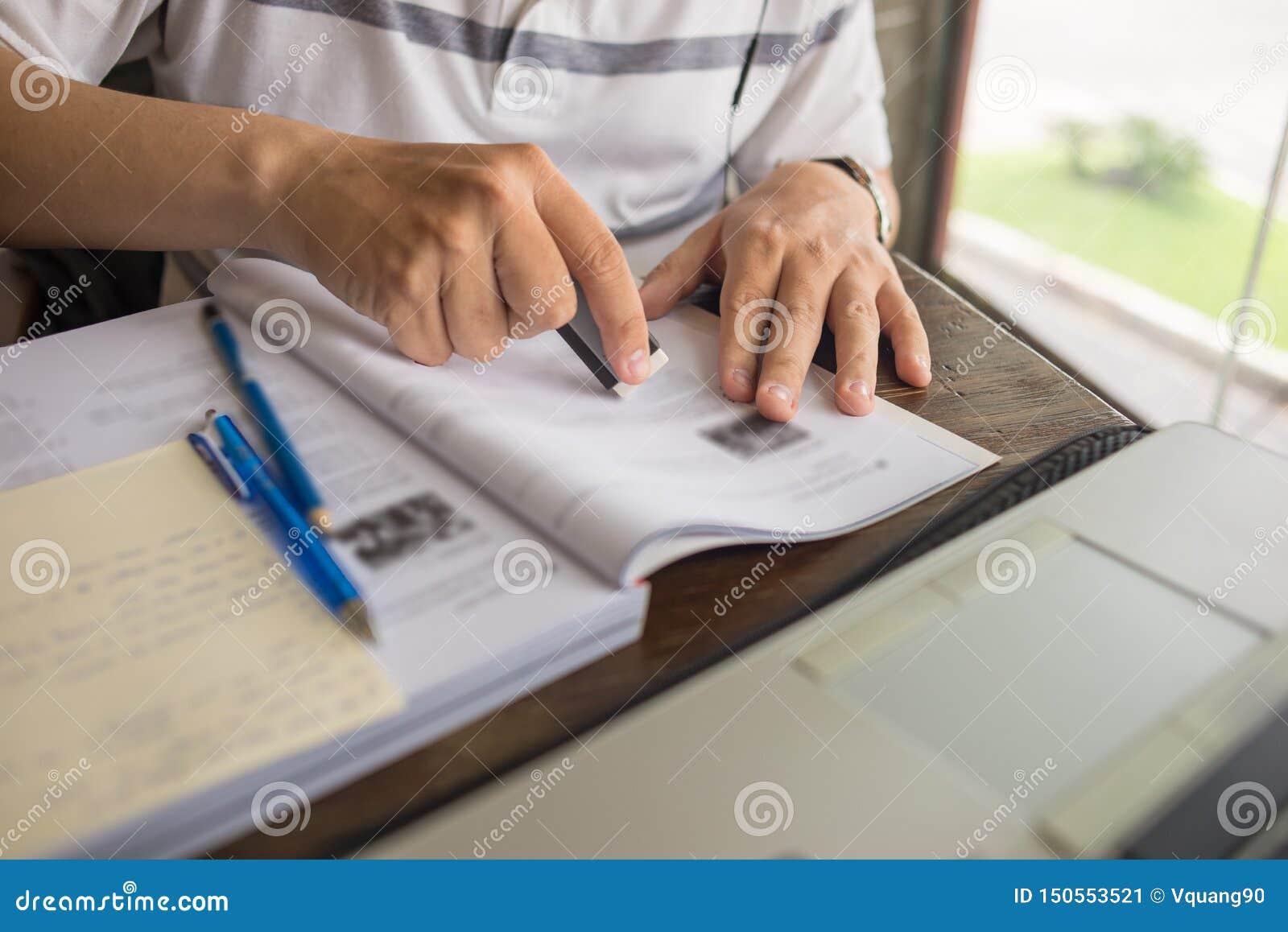 Nahaufnahme der Studentenhand unter Verwendung des Radiergummis auf Arbeitsbuch beim Studieren