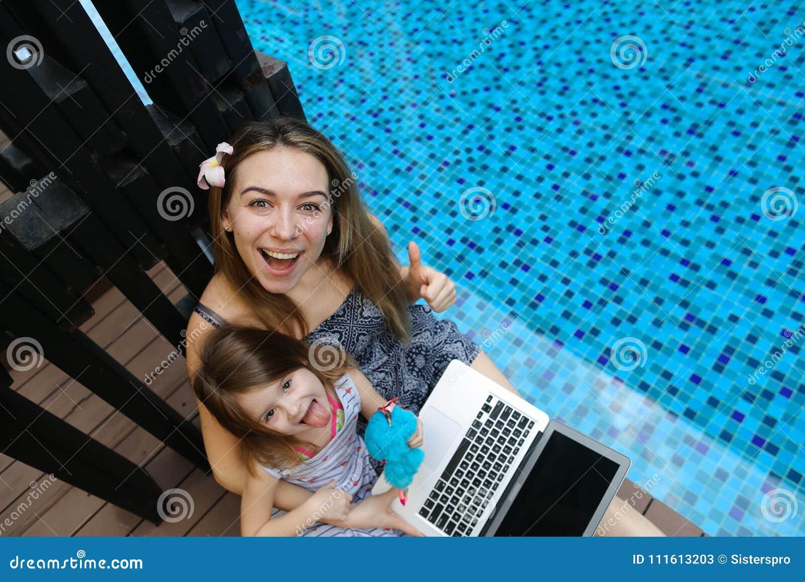 Nahaufnahme der weiblichen Mutter, der Tochter und des Laptops auf Hintergrund des Swimmingpools