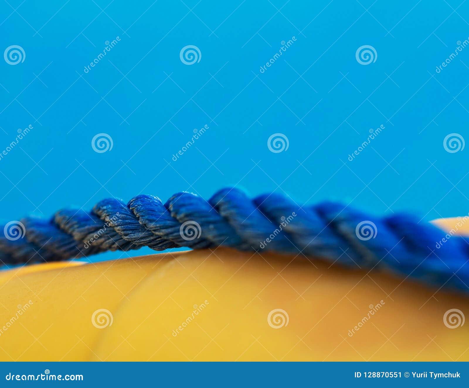 Nahaufnahme des blauen verdrehten Marineseils auf gelbem Rettungsring, flache Abteilung des Feldes