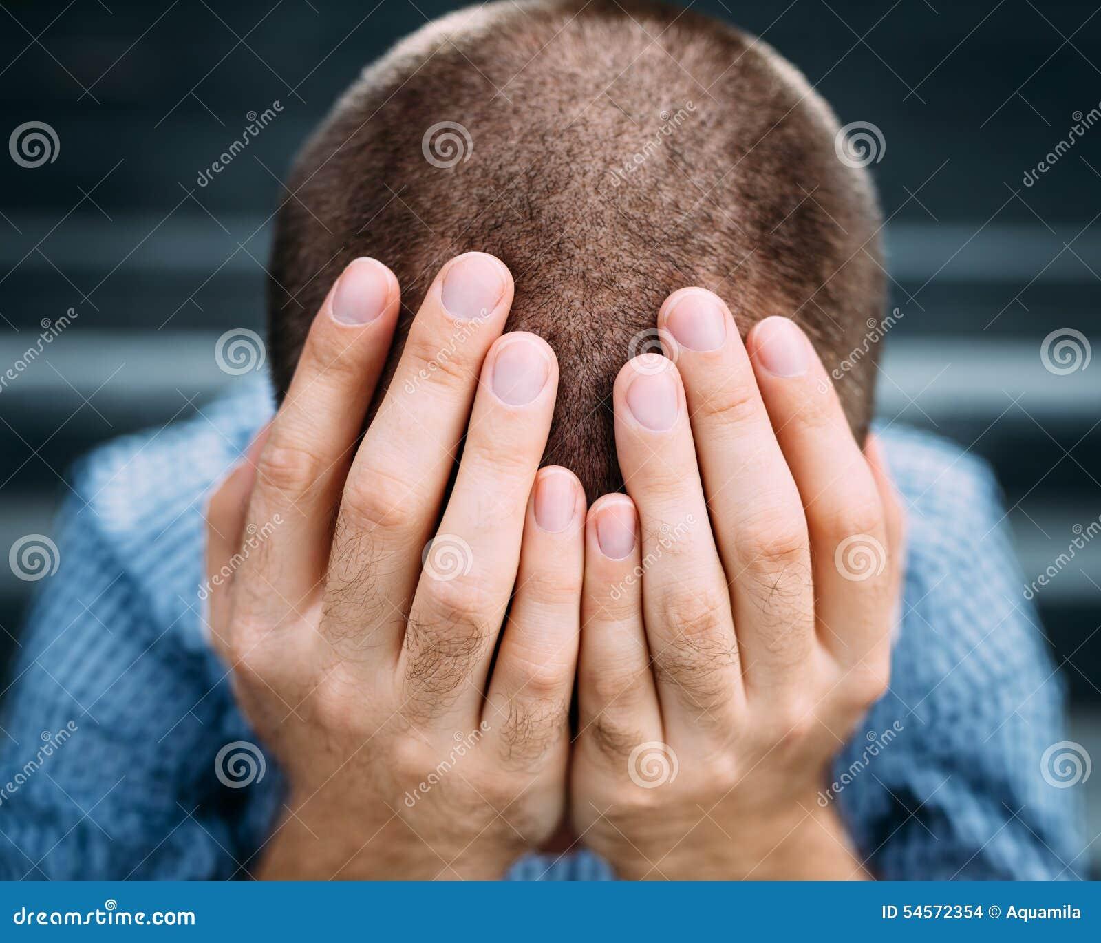 Nahaufnahme des verzweifelten jungen Mannes, der sein Gesicht mit den Händen bedeckt