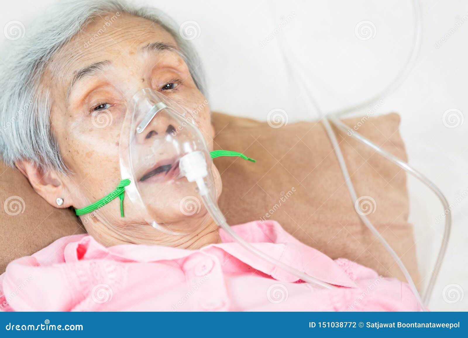 Nahaufnahme des weiblichen älteren Patienten, der Einatmungs- oder Sauerstoffmaske ins Krankenhausbett oder in Haus, krankes älte