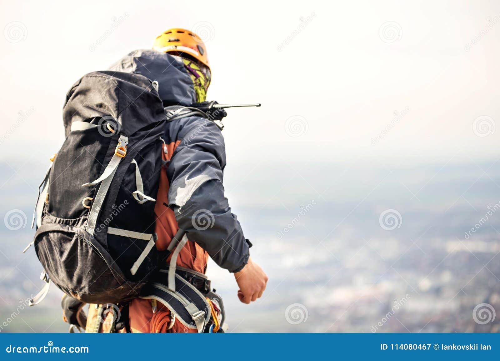 Nahaufnahme eines Bergsteigers von der Rückseite im Gang und mit einem Rucksack mit Ausrüstung auf dem Gurt, Stände auf einem Fel