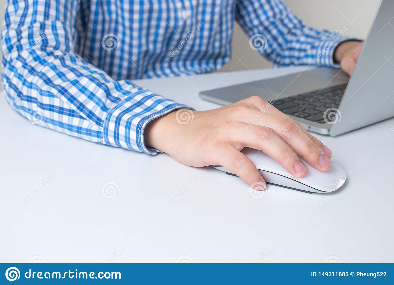 Nahaufnahme eines Mannes, der ein blaues kariertes Hemd unter Verwendung einer Hand h?lt die Maus im B?ro tr?gt