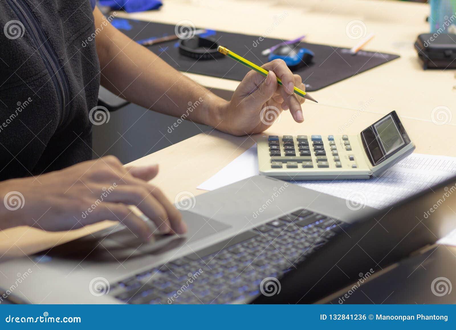 Nahaufnahme-Geschäftsmann, der Taschenrechner und conmputer Laptop für c verwendet