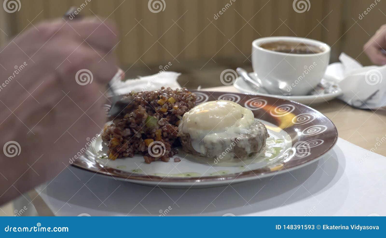 Nahaufnahme 4K der Mann isst roten Reis mit pochierten Rindfleischsteak und -ei, dem mit Gem?se